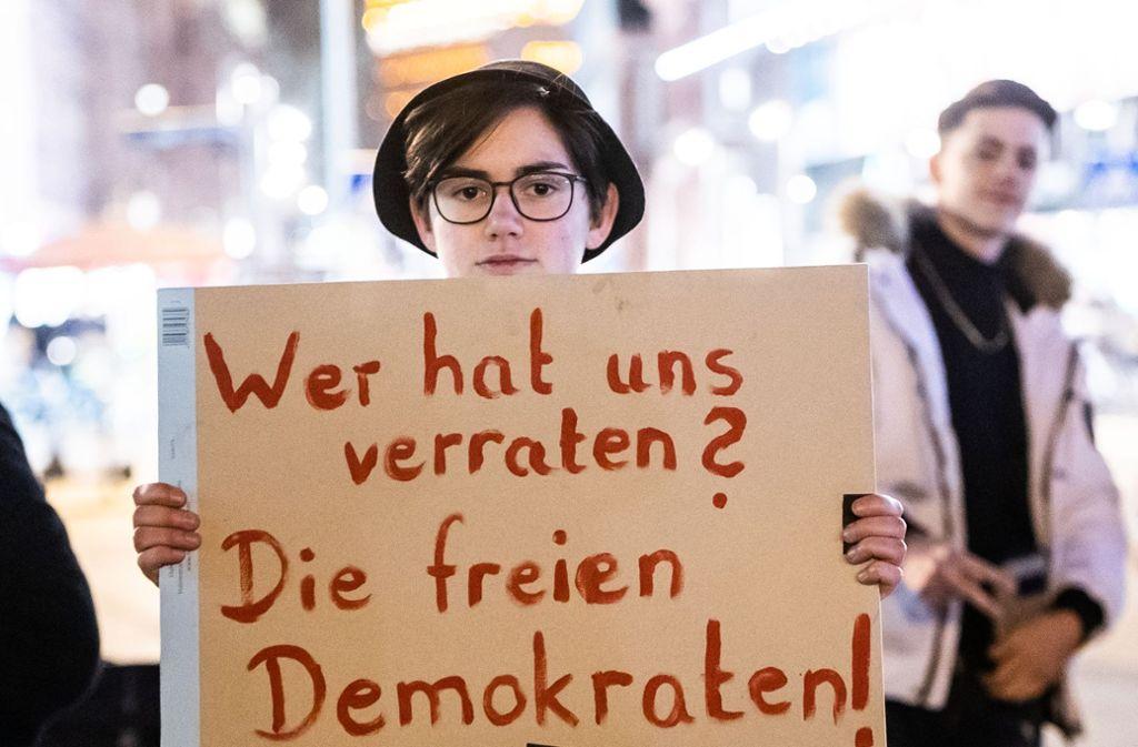 Eine Demonstrantin am Mittwochabend in Frankfurt. Unsere Bilderstrecke zeigt, was im Erfurter Landtag passiert ist. Foto: dpa/Andreas Arnold