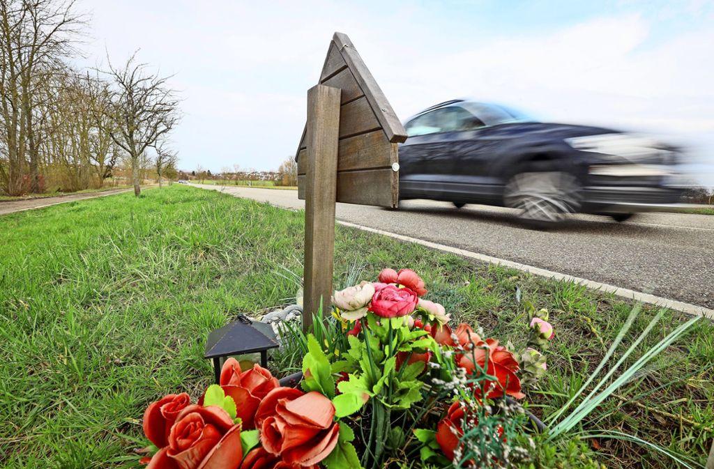 Eine hölzerne Tafel, Laternen  und Plastikblumen am  Straßenrand vor dem Anstieg nach  Löchgau: Auch hier gab es einen tödlichen Unfall Foto: factum/Simon Granville