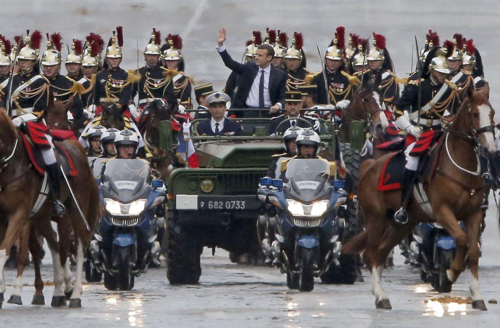Große Inszenierung: Begleitet von Reitern der Ehrengarde und Polizeimotorrädern fährt der neuefranzösische Präsident Emmanuel Macron  in einem Militärfahrzeug  über die Champs-Elysees. Foto: AP