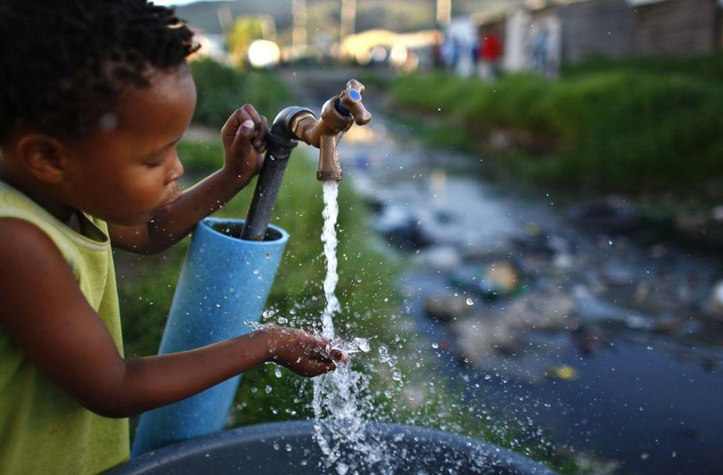 Ein Junge trinkt aus einer kommunalen Quelle in Kapstadt. Seit Monaten sind die Bewohner der südafrikanischen Metropole zum strengen Wassersparen angehalten. Foto: