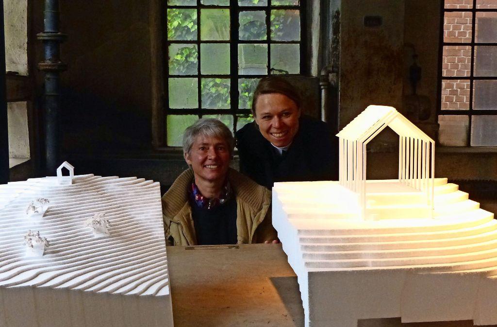 Karin Fendt (re.) und Veronique Faucheur mit dem reduzierten Haus (Modell rechts) und den Pflückgärten am Hang (Modell links). Foto: