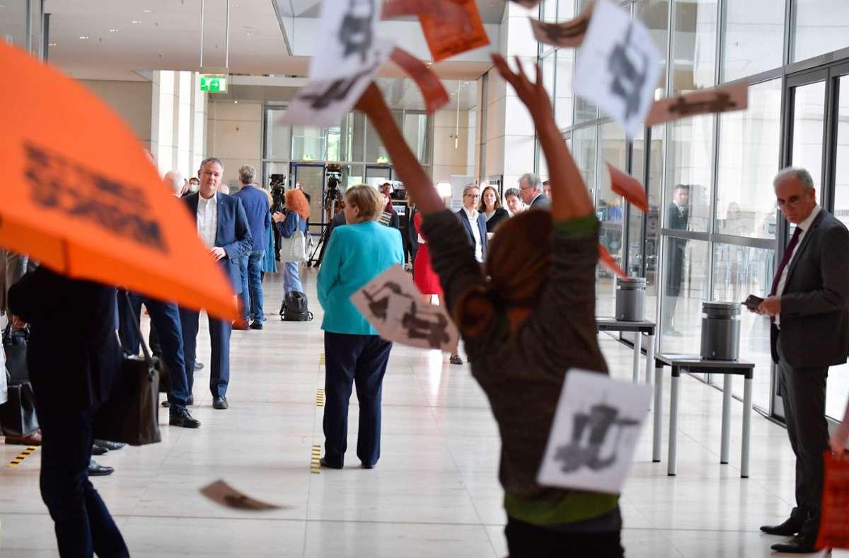 Protest vor den Augen Angela Merkels. Foto: AFP/TOBIAS SCHWARZ