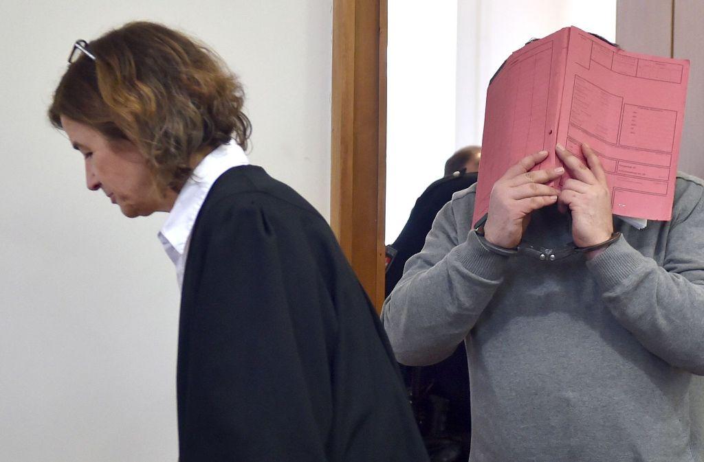 Der ehemalige Pfleger Niels H. versteckt sich bei einem Gerichtstermin in Oldenburg hinter einer Mappe, links im Bild seiner Verteidigerin Ulrike Baumann. Foto: DPA