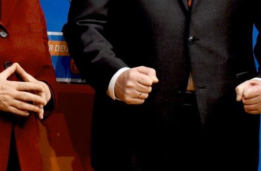 """Verräterische Körpersprache:  während Angela Merkels   """"Raute"""" dokumentiert, dass sie Politik wie immer betreibt, ballt Horst Seehofer   kampfeslustig die Fäuste. Foto: dpa"""