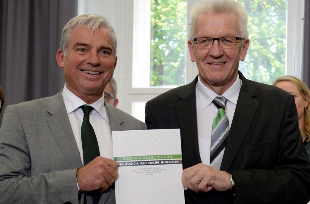 Ministerpräsident Winfried Kretschmann (rechts) und Innenminister Thomas Strobl mit dem Koalitionsvertrag. Foto: dpa