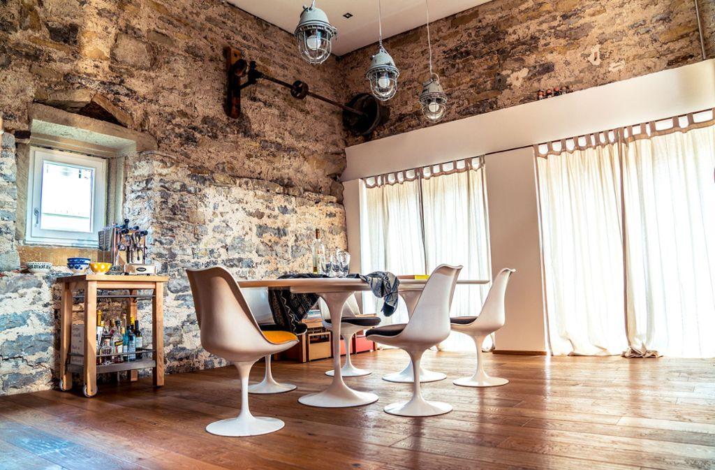 So architektonisch anspruchsvoll und stylish kann  eine Scheune sein: hohe Natursteinwände, neue Fenster und Türen, Eichendielen und Designklassiker von Eero Saarinen. Foto: Andy Wirth / PhotoART