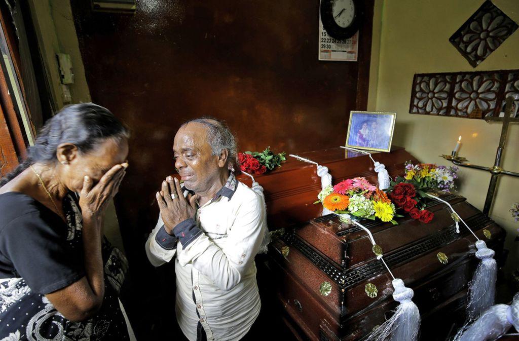 Eine sri-lankische Familie trauert neben den Särgen ihrer drei Familienmitglieder, die alle Opfer des Bombenanschlags am Ostersonntag waren. Foto: Eranga Jayawardena/dpa