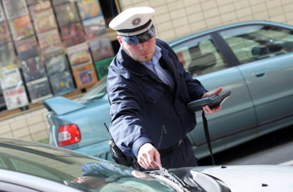 Ärgerlich für jeden Autofahrer: ein Polizist verteilt ein Knöllchen. Foto: dpa