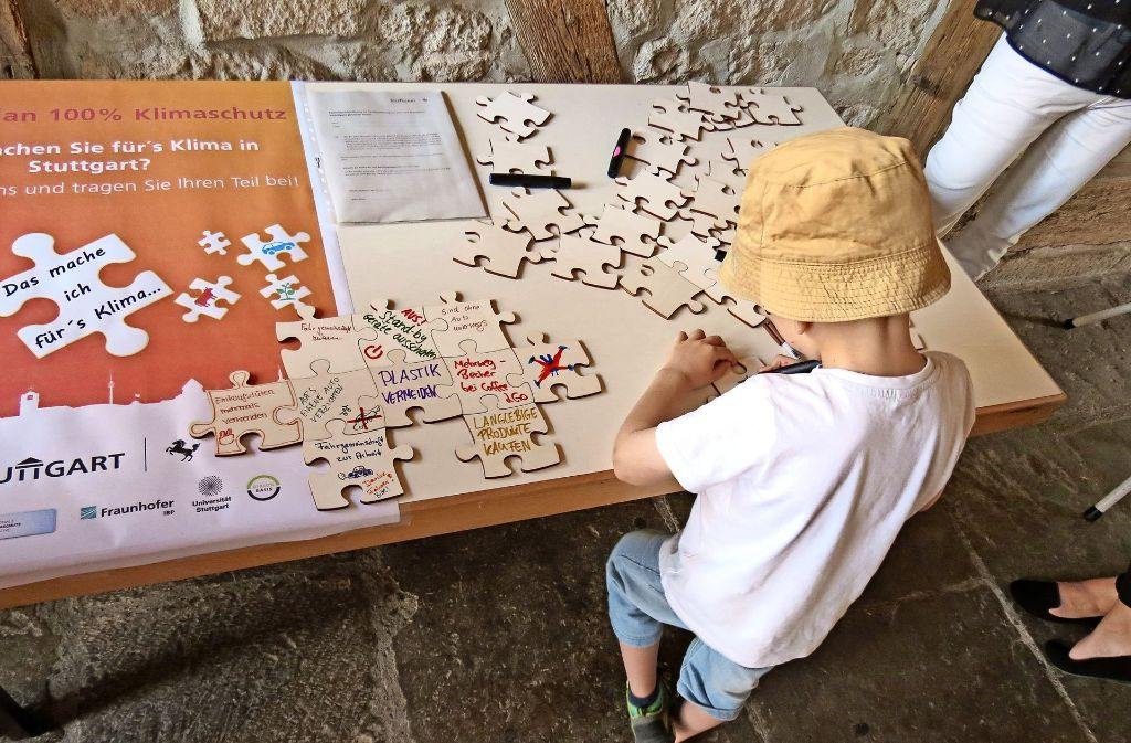 Plastik vermeiden, aufs Auto verzichten und Mehrwegbecher: Auf Puzzleteilen konnten Schlagwörter notiert werden. Davon machten auch kleine Besucher Gebrauch. Foto: Julia Bosch