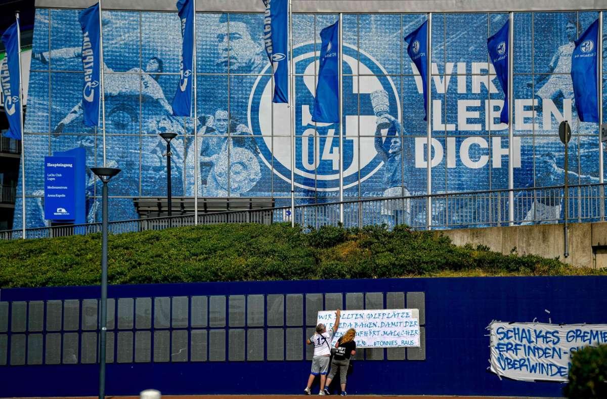 Fans hängen Protest-Plakate vor das Stadion: Seit Wochen ist der Verein in der Krise – nicht nur sportlich. Foto: AFP/SASCHA SCHUERMANN