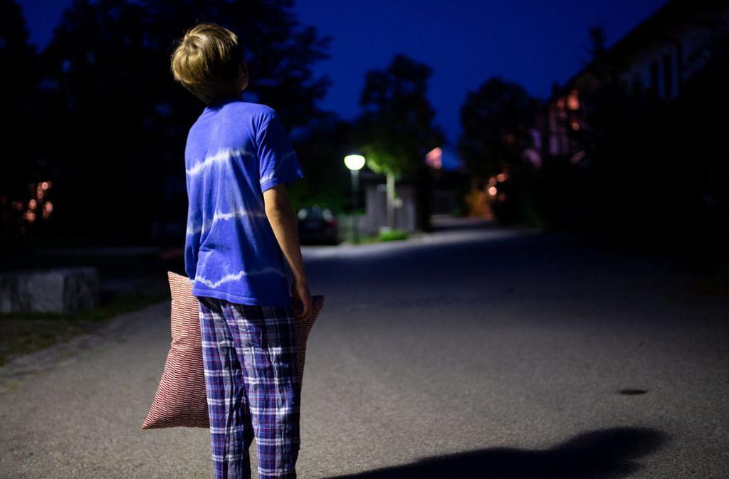 Ein Junge im Schlafanzug steht nachts mit einem Kissen in der Hand auf einer Straße. Während andere tief und fest schlafen, laufen sie oft zur Hochform auf, wenn auch unfreiwillig: Schlafwandler. Foto: dpa