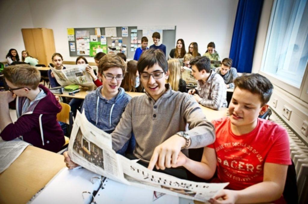 Die Schüler der Klasse 9c am Königin-Katharina-Stift in Stuttgart werfen einen ersten Blick in die Stuttgarter Zeitung. Foto: Lichtgut/Max Kovalenko
