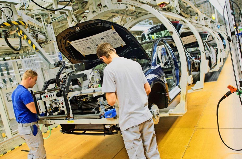 VW-Mitarbeiter arbeiten im Volkswagen-Werk in Wolfsburg (Niedersachsen) an einem Golf VII. Foto: dpa