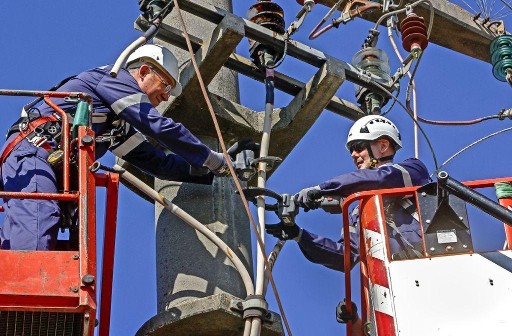 Oberbürgermeister Martin Kaufmann (rechts) und Netze BW-Geschäftsführer Christoph Müller durchtrennen das letzte Kabel der ehemaligen Freileitung. Foto: factum/Bach