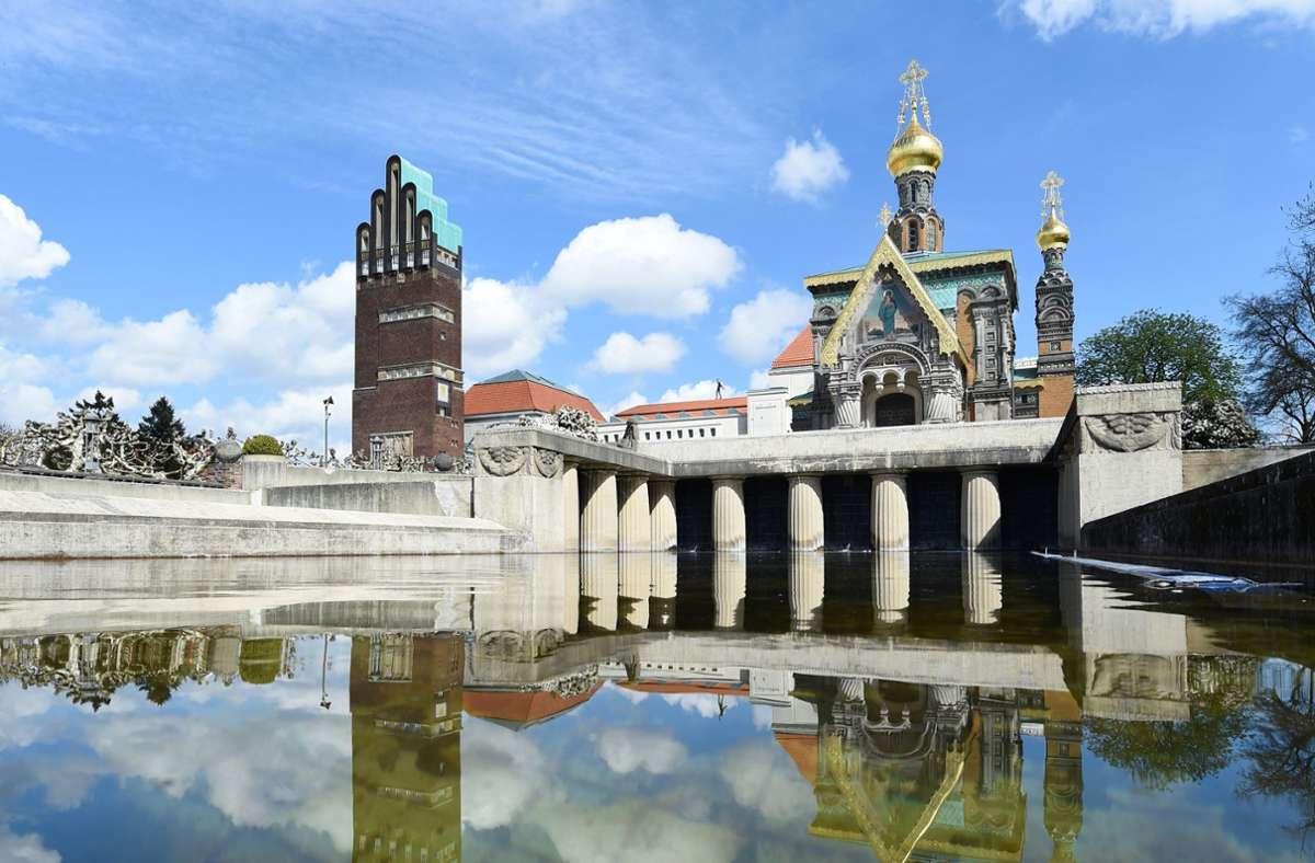 Der Hochzeitsturm (links), das Ausstellungsgebäude und die russische Kirche spiegeln sich auf der Mathildenhöhe in Darmstadt. Die Künstlerkolonie gehört nun zum Weltkulturerbe. Foto: dpa/Arne Dedert