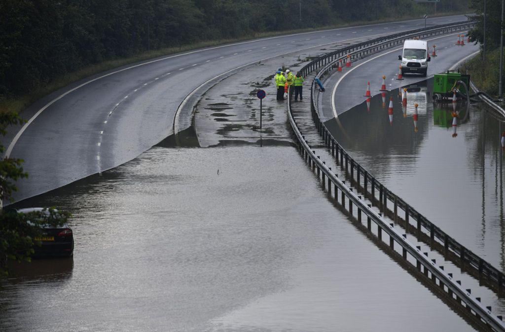 Land unter: Polizisten sperren die überschwemmte A 555  nahe Manchester Foto: dpa