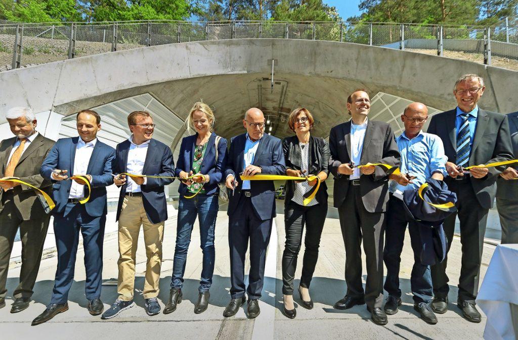 Der Verkehrsminister Winfried Hermann (Mitte) und andere Ehrengäste schnitten das Band am Tunnel durch. Foto: factum/Granville