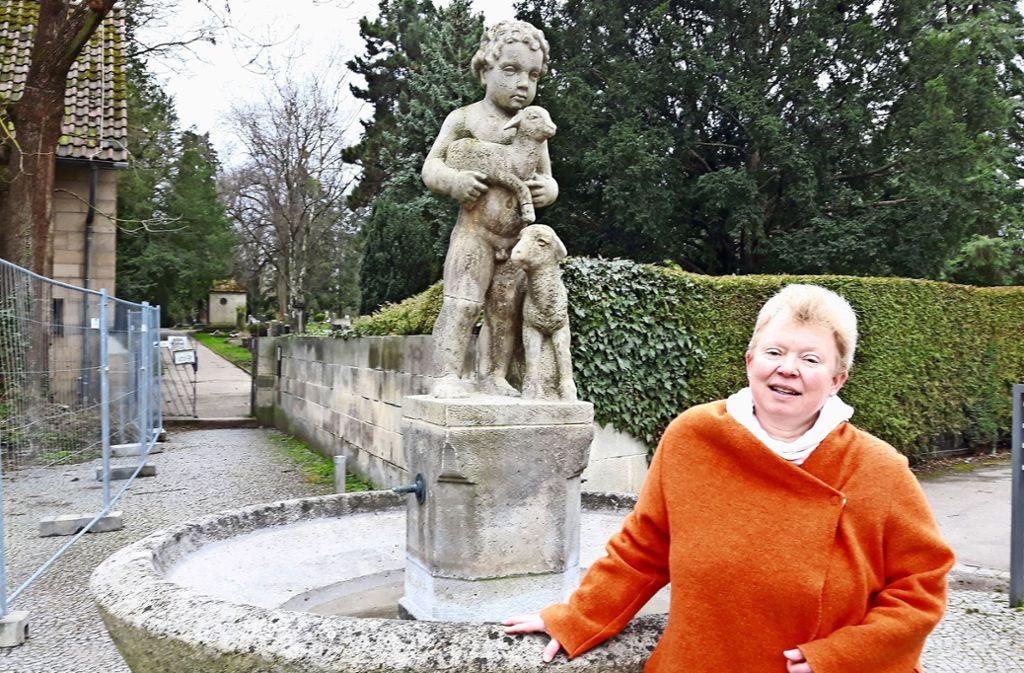 Pfarrerin Rommel am Wahrzeichen der Gemeinde: dem Gute-Hirte-Brunnen Foto: Eva Funke