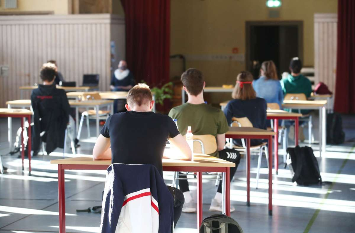 Schüler mit Mundschutz sitzen bei der Prüfungsvorbereitung fürs Abitur in einer zum Schulraum umfunktionierten Turnhalle. Foto: picture alliance/dpa/Bodo Schackow