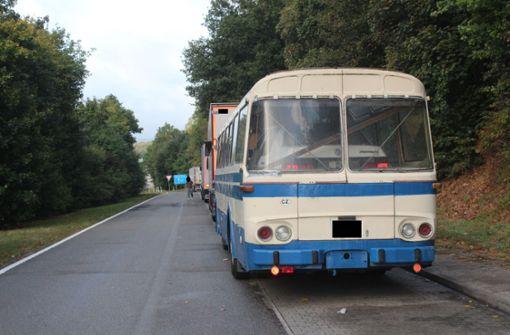 Mann lädt Auto in Reisebus und fährt damit über die Autobahn