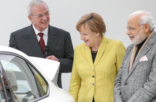 Winterkorn und Merkel zeigen Poker Face