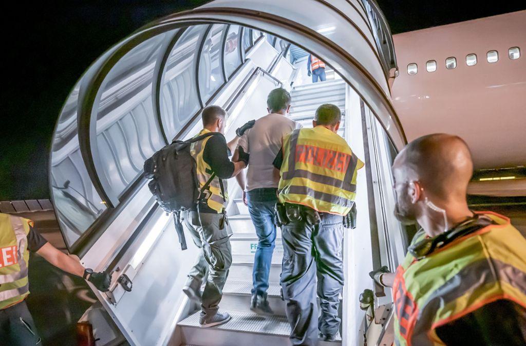 Polizeibeamte begleiten einen Migranten in Leipzig in ein Charterflugzeug. Foto: dpa/Michael Kappeler