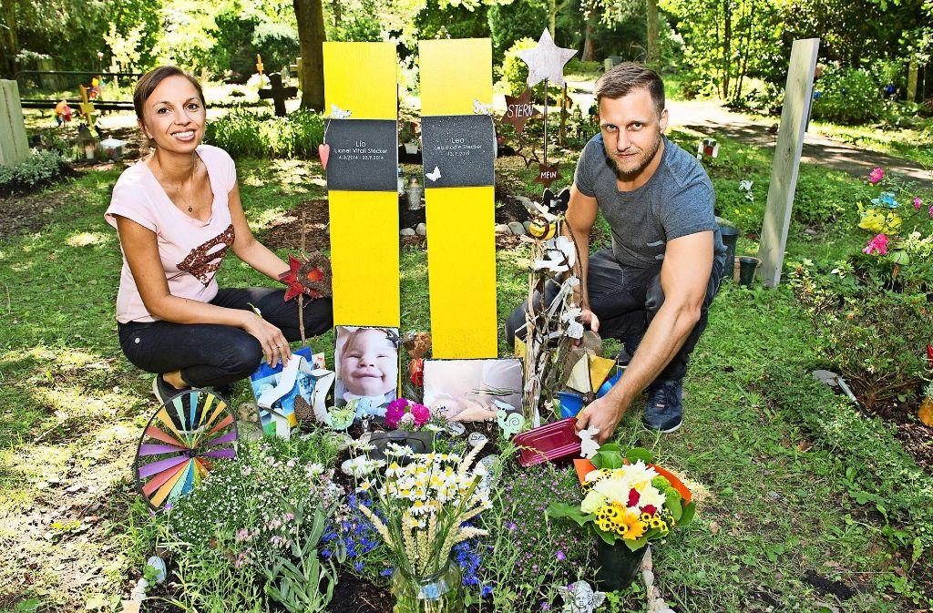 Hannah und Thorsten Stecker legen die neue Box aufs Grab ihrer Kinder. Foto: Lg/Willikonsky
