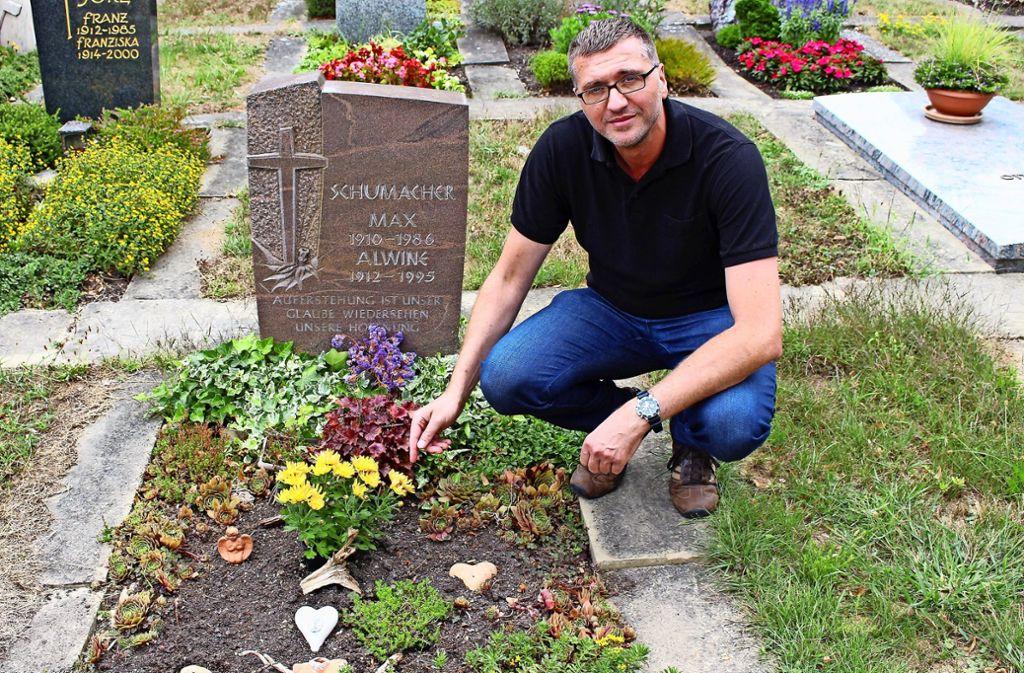 Frank Laux am Grab seiner Großeltern. Die Blumen, die mittig saßen, sind zerstört worden. Foto: Caroline Holowiecki