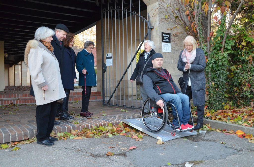 Ivo Josipovic testet die mobile Rampe am Alten Friedhof. Die Besucher des Friedhofs finden die Rampe, die Gabriele Leitz (rechts) mitgebracht hatte,  eine sinnvolle Idee. Foto: Sandra Hintermayr