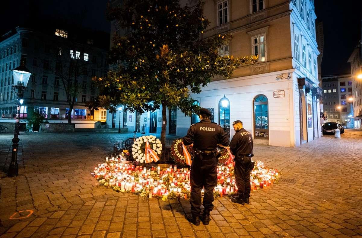 Polizisten stehen vor Kerzen am Tatort Desider-Friedmann-Platz in der Wiener Innenstadt, wo vor rund acht Monaten ein Anschlag verübt wurde. (Archivbild) Foto: dpa/Georg Hochmuth