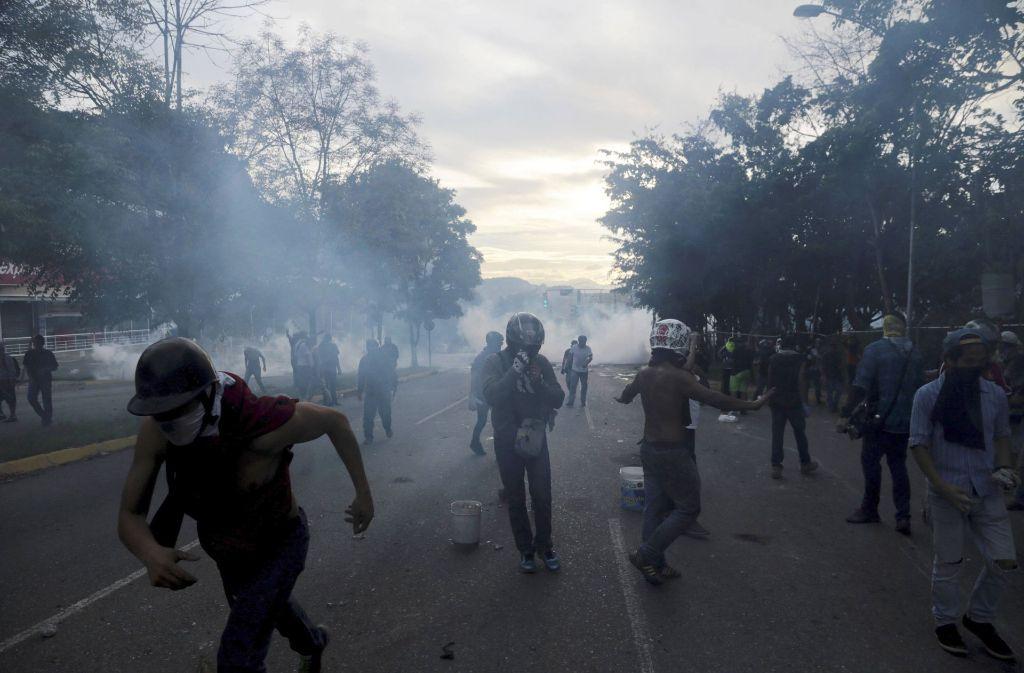 Demonstranten bringen sich in Caracas, Venezuela, während Zusammenstößen mit der Bolivarianische Nationalgarde in Schutz. Die Proteste richten sich gegen den sozialistischen Präsidenten Maduro. Foto: AP