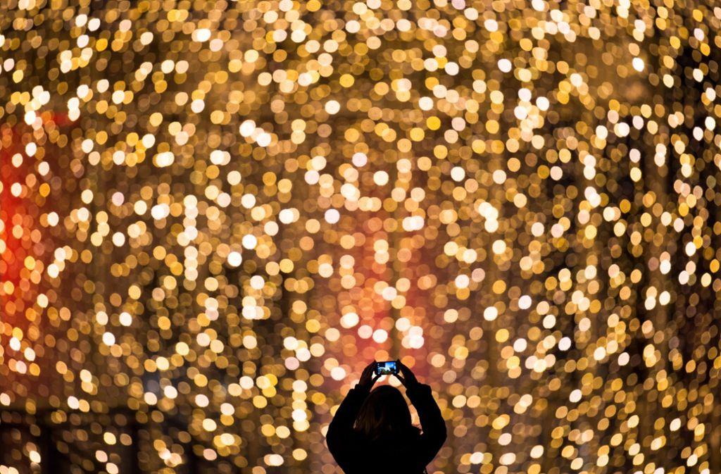 Was ist von Weihnachten geblieben außer Konsumrausch und arbeitsfreie Tage? Eine Frau fotografiert die Fassade des mit Lichterketten weihnachtlich geschmückten Einkaufszentrums Hamburger Meile. Foto: dpa