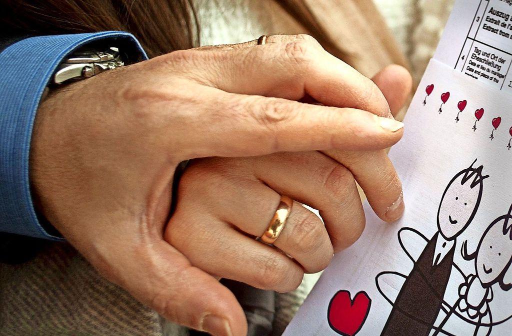 Ein frisch vermähltes Ehepaar hält seine Heiratsurkunde in den Händen. Foto: dpa