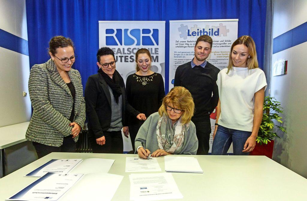 Die Partnerschaft  ist besiegelt: Christina Almert unterzeichnet den Vertrag. Marion   Oker, Tamara  Rumpelt, Lisa Almert, Hannes Dreja und Selina Schoer, beide für  Berufsorientierung an der Realschule zuständig (von links), begrüßen die  Zusammenarbeit. Foto: factum/Bach