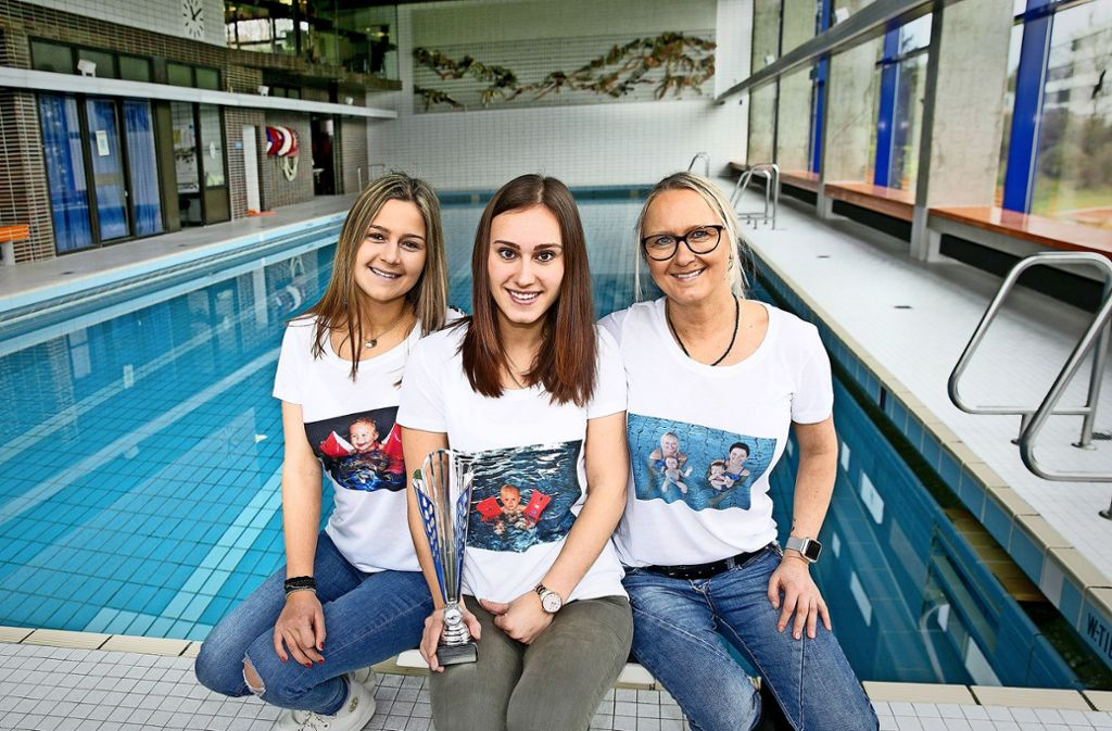 Die beiden Ex-Babyschwimmerinnen Anna Hogh und  Corinna Mödinger  mit der  Trainerin Nicole Hogh (von links) in T-Shirts mit alten Fotos vom Winter  1997/98 Foto: Horst Rudel