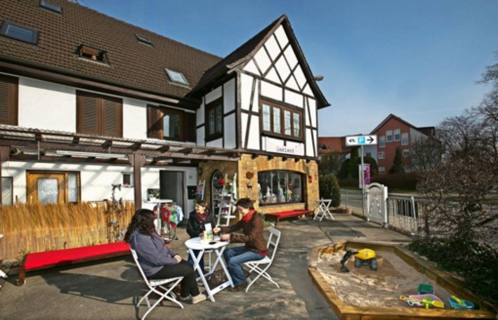 Vor dem kleinen Fachwerkhaus laden weiß lackierte Stühle und Tische zum Verweilen in der Frühlingssonne ein. Derweil kann der Nachwuchs im Sandkasten spielen. Foto: Horst Rudel(2), fotolia