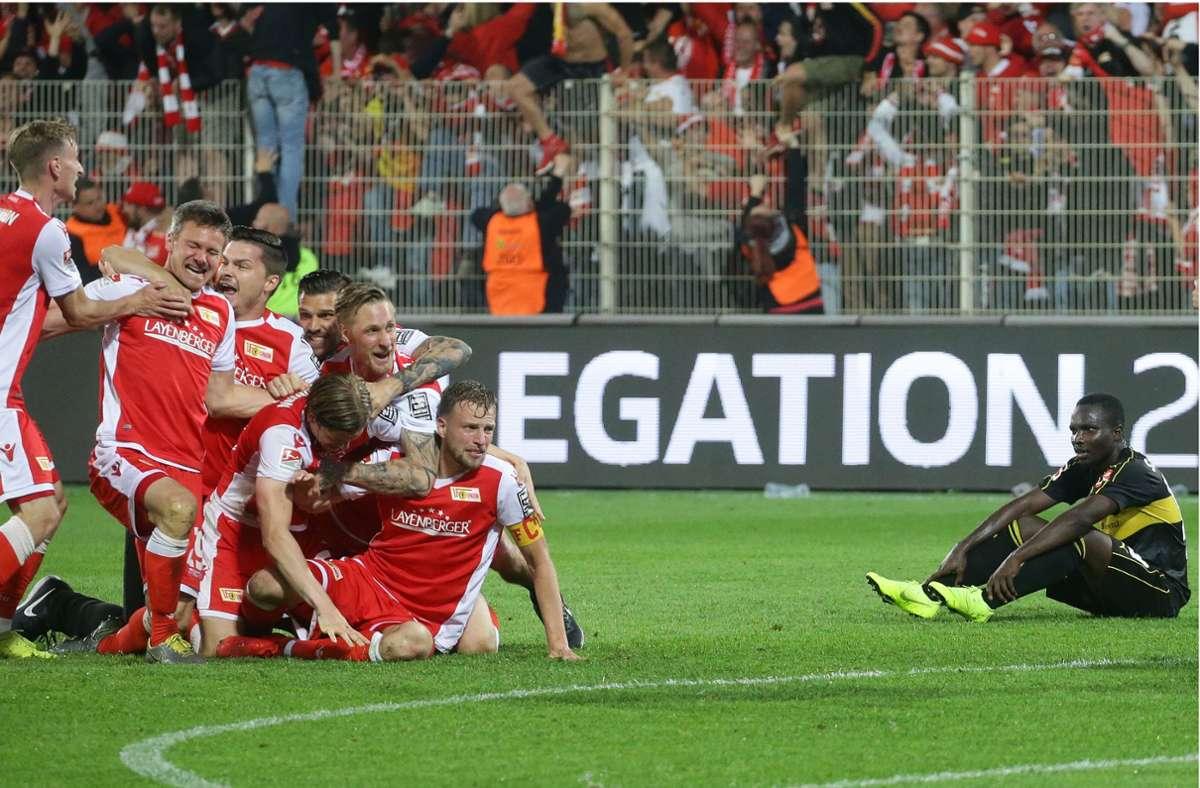 Die Union-Spieler feiern 2019 ausgelassen –  Chadrac Akolo (re.) und der VfB Stuttgart sind am Boden. Dass sich der Zweitligist in den Relegationsspielen durchsetzt, kommt selten vor. Foto: Baumann
