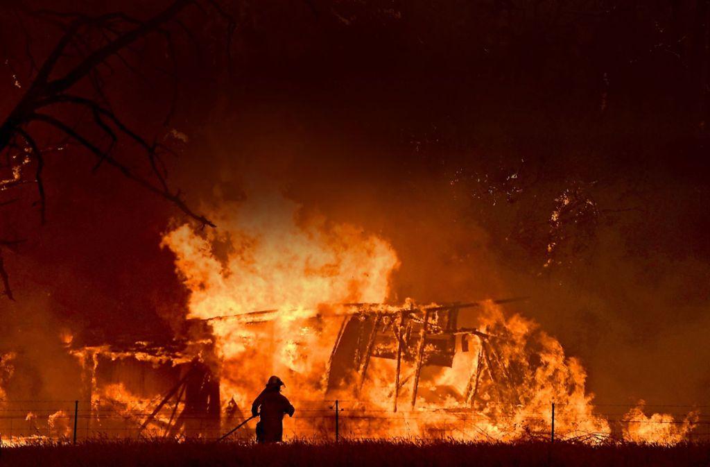 Ein Feuerwehrmann bekämpft in Australien die Flammen eine Buschfeuers, die  ein Gebäude erreicht haben. Foto: AAP/dpa/Dan Himbrechts
