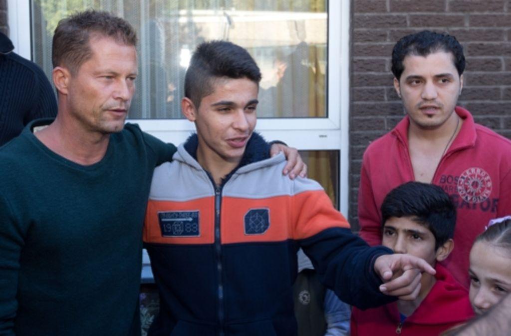 Der Schauspieler Til Schweiger (links) steht am 30. September vor einem Flüchtlingshaus in Osnabrück neben Flüchtlingen. Schweiger will sich mit seiner «Til Schweiger Foundation» für Flüchtlings-Kinder einsetzen. Foto: dpa