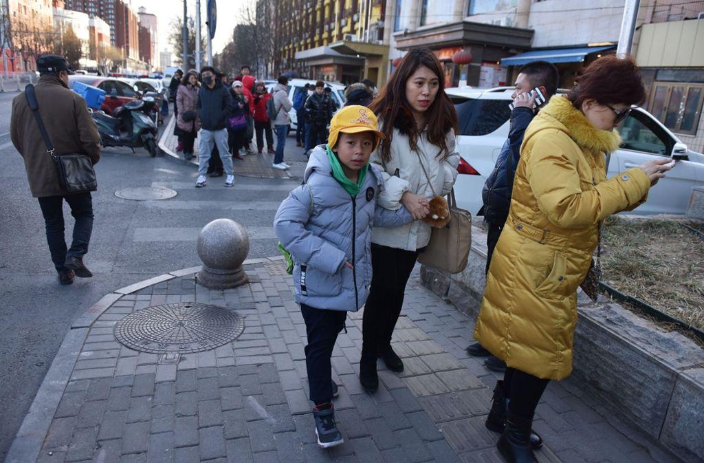 Eine Frau kümmert sich in Peking um einen Schüler. Foto: AFP