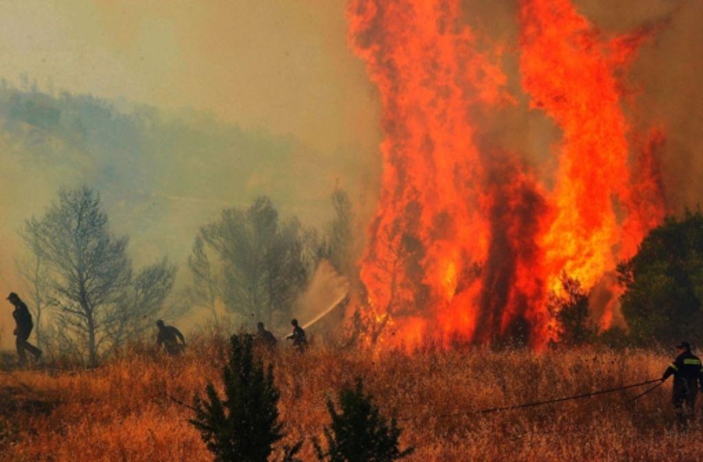 Feuerwehrmänner versuchen in der Nähe von Korinth einen Brand zu löschen. Foto: ANA-MPA