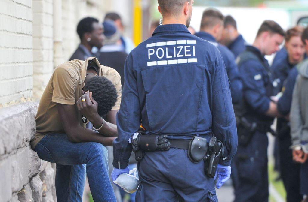 Polizisten überwachen während einer Drogenrazzia in einer Landeserstaufnahmestelle Verdächtige. Foto: dpa