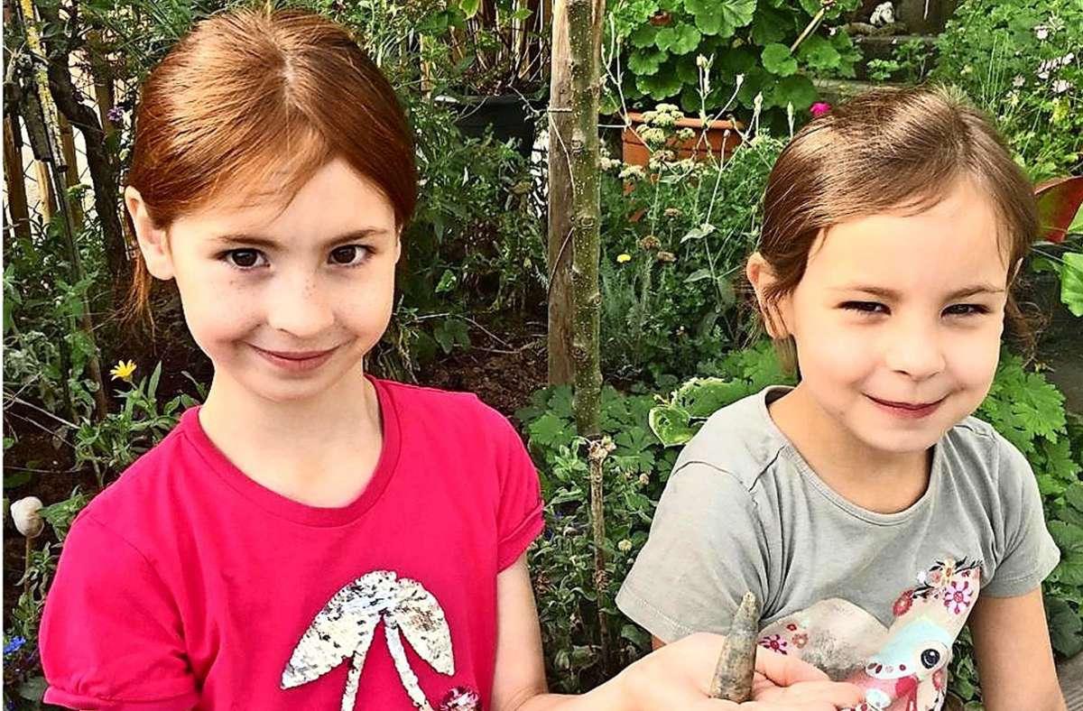"""Neele (links) und Hannah Förster zeigen den """"Donnerkeil"""", den sie in ihrem Garten gefunden haben. Foto: privat/Sören Förster"""