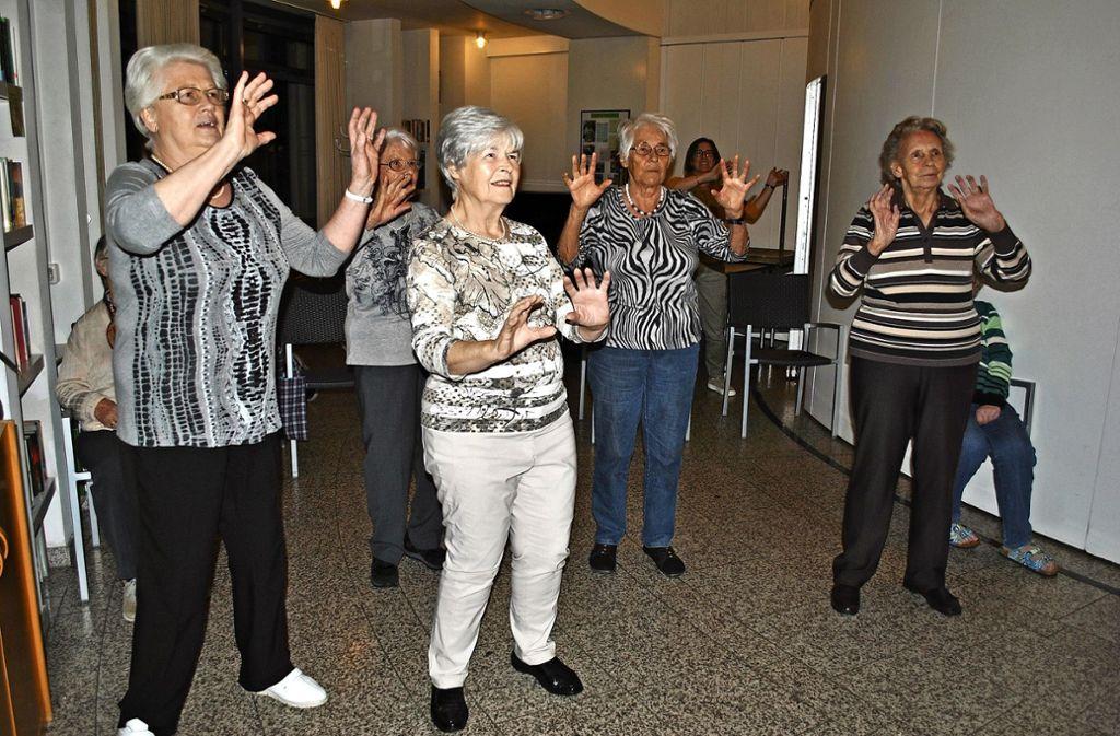 Konzentriert machen die Teilnehmer die Tanzbewegungen auf dem Bildschirm nach. Foto: