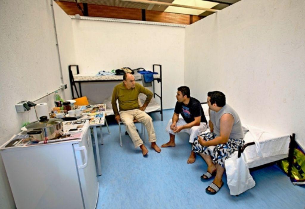 Jeweils drei  Flüchtlinge teilen sich  in der Schulsporthalle in Esslingen-Zell eine der  35 nach oben offenen Kabinen. Da bleibt wenig Raum für die Privatsphäre. Foto: Horst Rudel