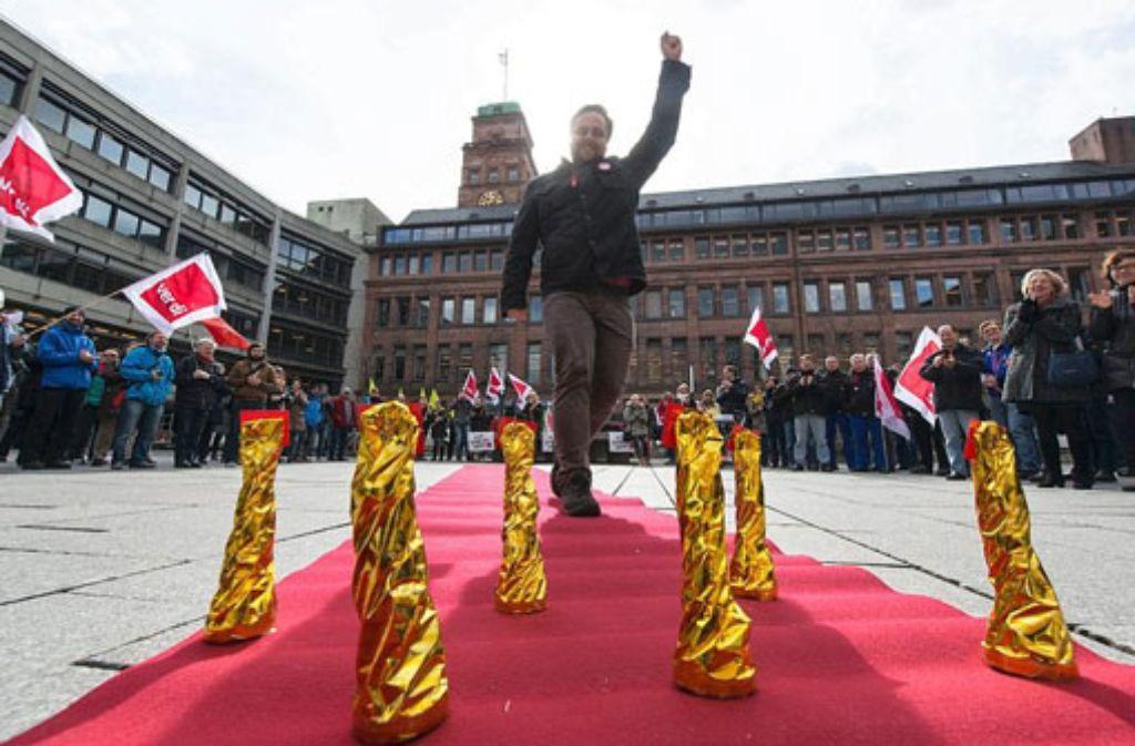 Ein Angestellter der Albert-Ludwigs-Universität Freiburg läuft am Mittwoch in Freiburg bei einer Verdi-Protestaktion über einen symbolischen roten Teppich. Foto: dpa