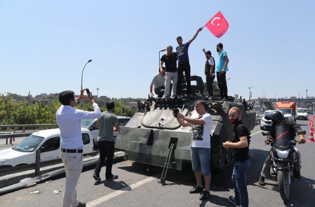 Nach dem gescheiterten Putsch lassen sich Menschen auf einem Panzer fotografieren. Foto: EPA