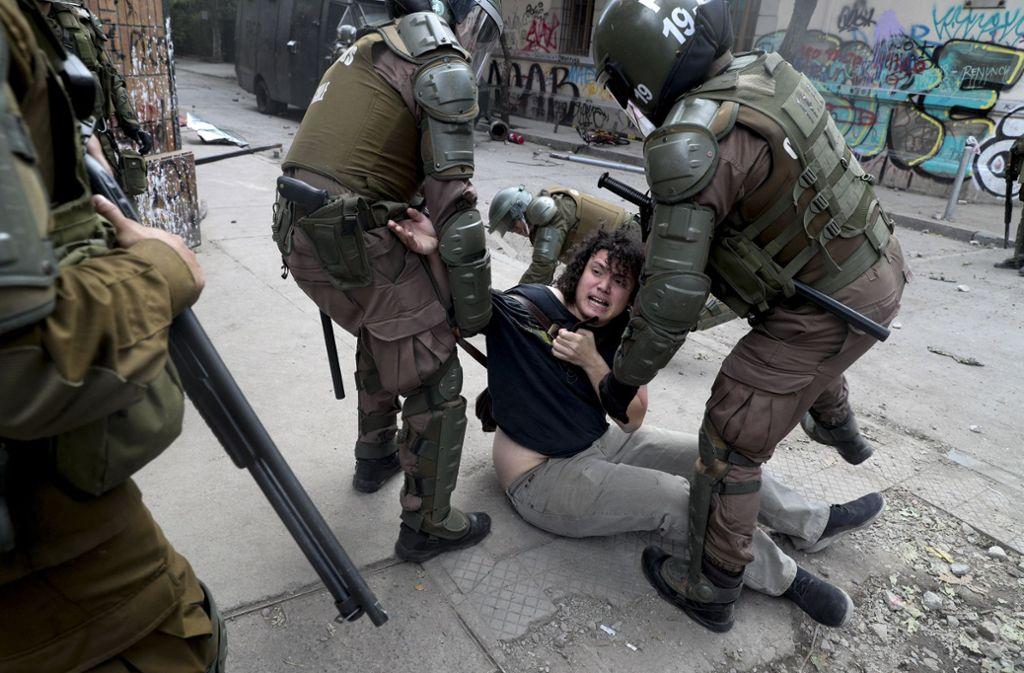 Polizisten nehmen während eines Protestes gegen die Regierung einen Demonstranten fest. Proteste gibt es in Chile seit gut zwei Wochen. Auslöser war eine geplante relativ geringe Erhöhung der Nahverkehrspreise. Foto: Esteban Felix/AP/dpa/Esteban Felix