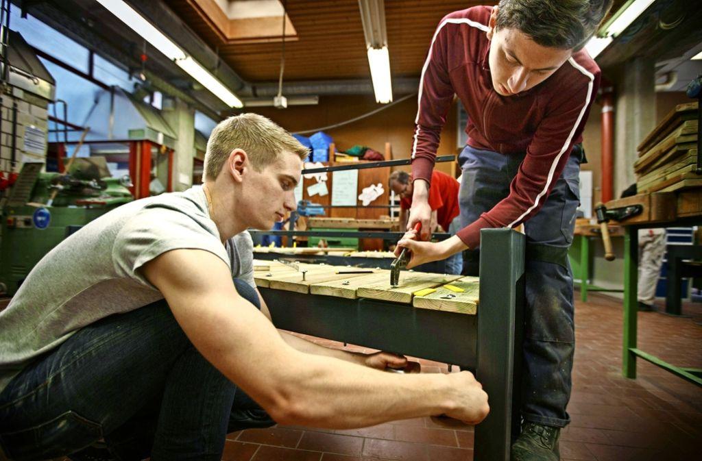 Daimler-Mitarbeiter legen beim Schafftag  an den Bänken im Berufsbildungswerk Waiblingen letzte Hand an. Foto: Gottfried Stoppel