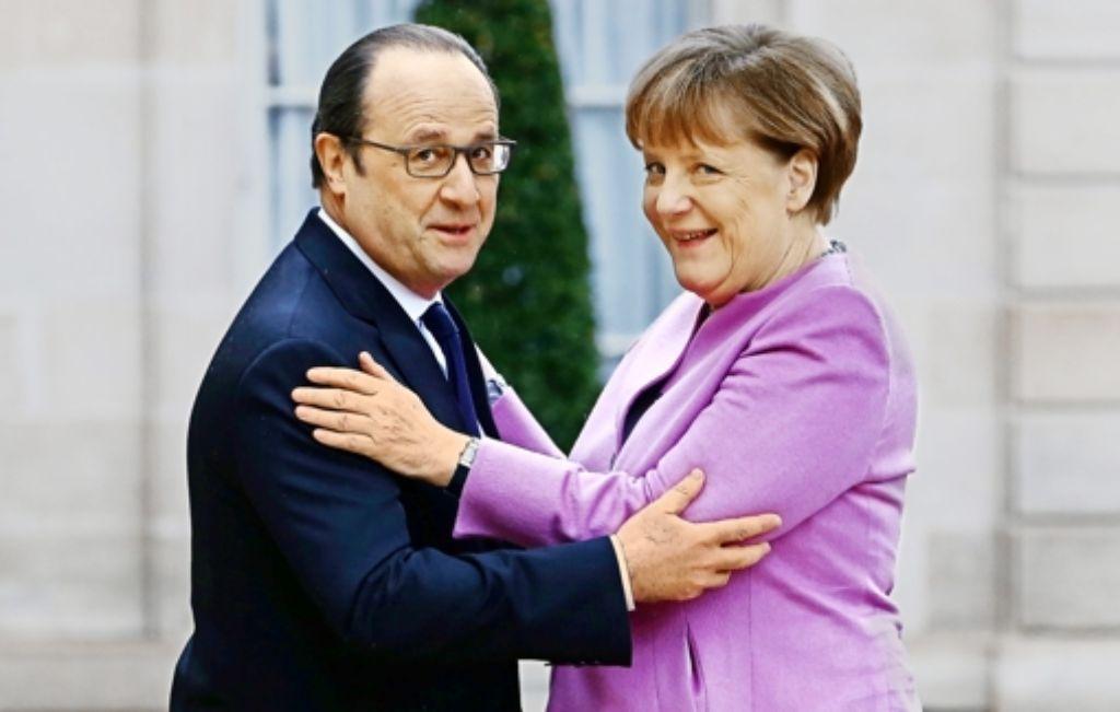 Optimismus verbreiten  in Paris:  Am Freitagmorgen umarmen sich François Hollande  und Angela Merkel     vor ihrem Treffen im Élysée-Palast. Foto: dpa